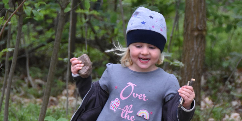 Ein Mädchen lacht und hat einen Stein und kleine Äste in der Hand im Hintergrund ist ein Wald zu sehen