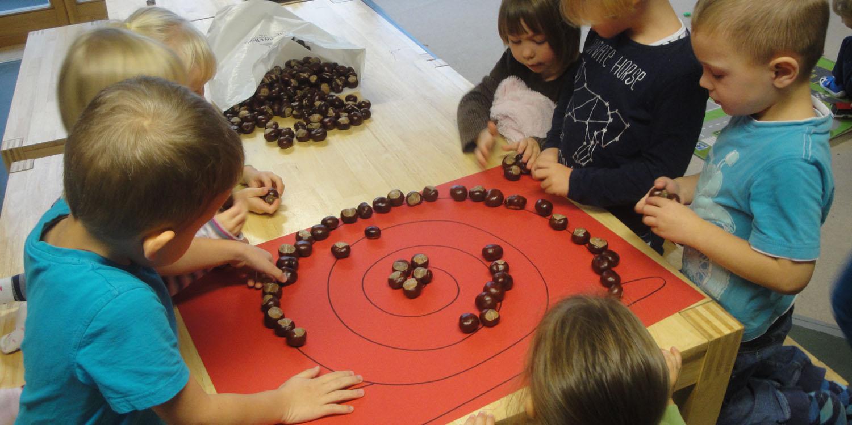 Mehrere Kinder legen auf einem Blatt Papier, wo eine Schnecke drauf gemalt ist, mehrere Kastanien hintereinander