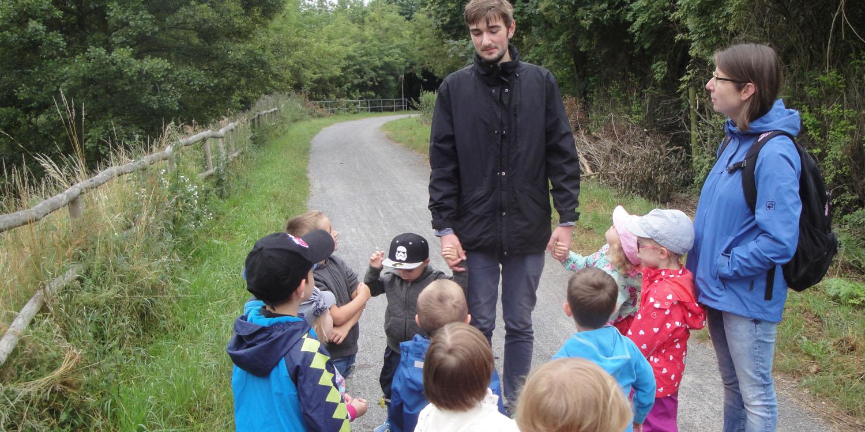 Mehrere Kinder stehen mit zwei Erziehern an einem Weg