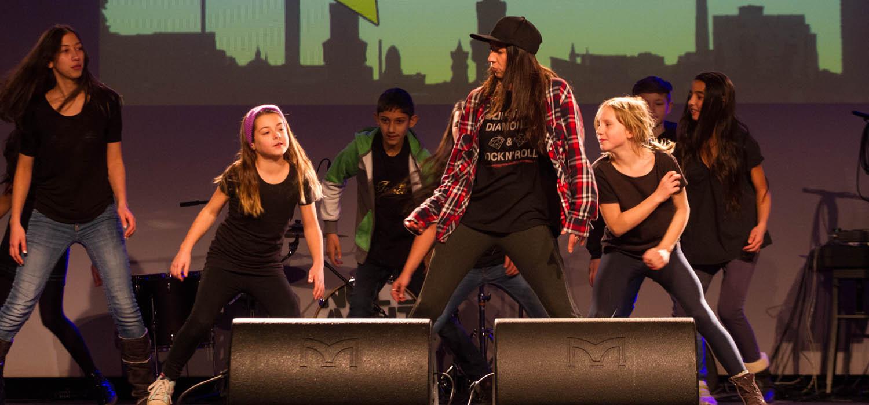 Schülerinnen und Schüler performen und tanzen bei einer Veranstaltunggegen Ausgrenzung und Rassismus.
