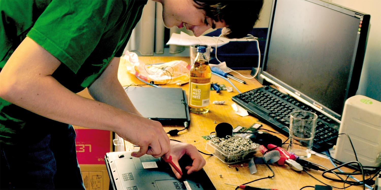 Auszubildender schraubt an einem PC