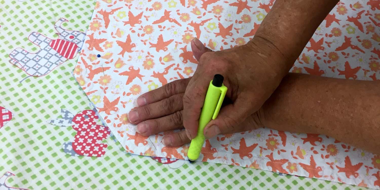 Nahaufnahme beim Zuschneiden eines Stück Stoffes in der Nähwerkstatt