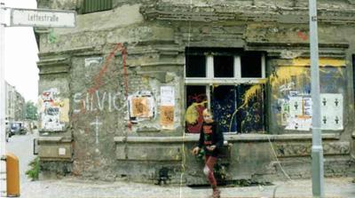 Ein junges Mädchen im Punkerlook steht vor einem verfallen Haus im noch nicht sanierten Bezirk Prenzlauer Berg.