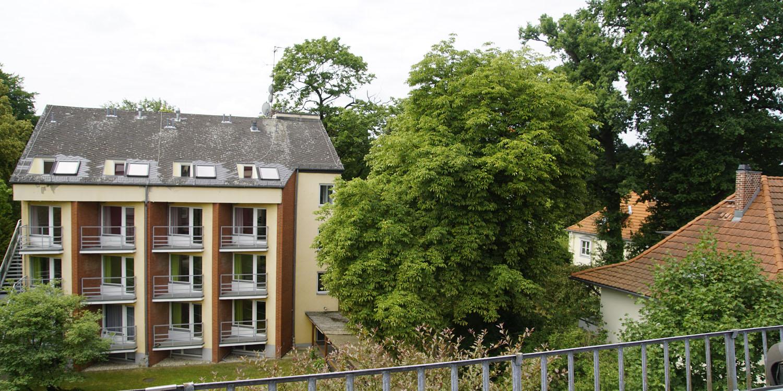 Blick aus dem Balkon auf einen grünen Garten mit Rasen und alten Bäumen sowie das Haus gegenüber