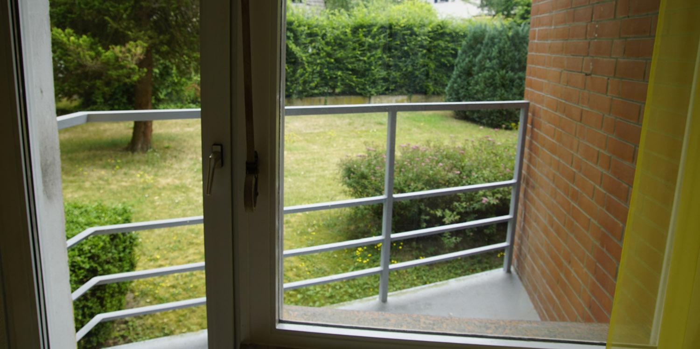 Blick aus dem Balkon in einen grünen Garten mit Rasenfläche und alten Bäumen