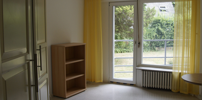 Blick in ein Zimmer mit einem schönen Balkonblick mit gelben Gardinen