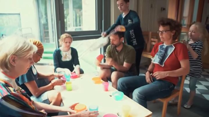Erwachsene sitzen an einem Tisch. Kinder binden ihnen ein Lätzchen um.