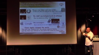 Idan Amiel steht auf einer Bühne und zeigt auf seine Präsentation.