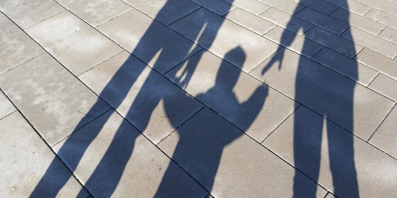 Schattensilhouette eines Kindes mit seinen Eltern, die es an der Hand fassen möchten und ihre Hände nach ihm ausstrecken.