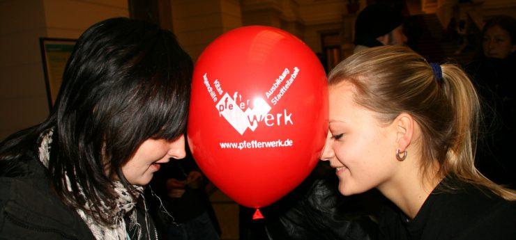 Zwei junge Frauen halten einen roten Luftballon mit weißem Pfefferwek-Logoaufdruck zwischen ihren beiden Gesichtern.