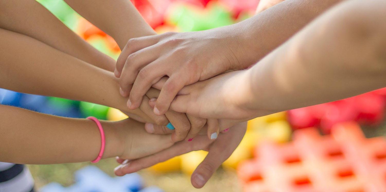 Wir halten zusammen - viele aufeinander gelegte Hände