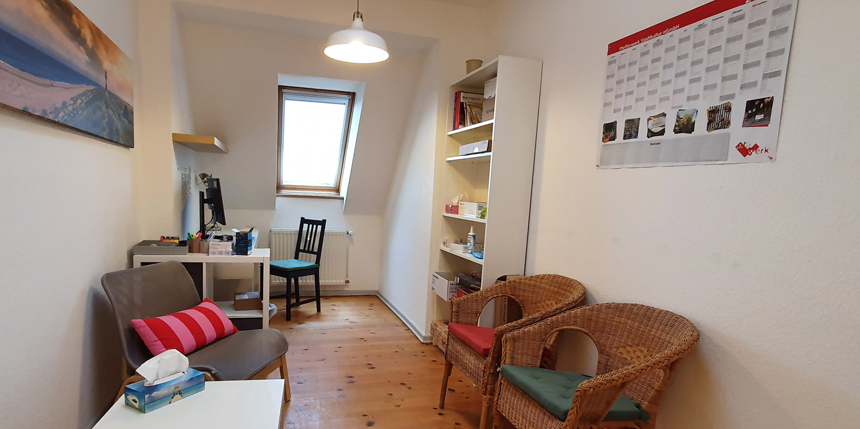 Büro im An der linken Wand und unter den beiden Fenstern stehen zwei Sofas mit einem kleinen Tisch. Im vorderen Bereich ein großer dunkelbrauner Tisch mit Stühlen.