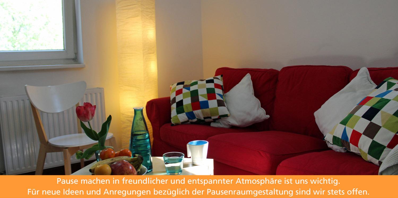 Im Pausenraum lädt ein rotes Sofa zum Entspannen ein. Auf einem viereckigen isch stehen eine Obstschale, Wasser und eine Vase mit einer Tulpe.