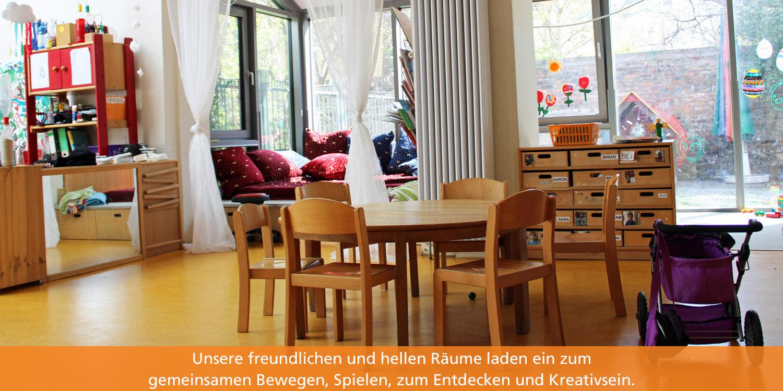 In dem Gruppenraum stehen ein runder Tisch und fünf kleine Stühle. Im Hintergrund stehen kleine Schränke mit Kreativmaterialien.