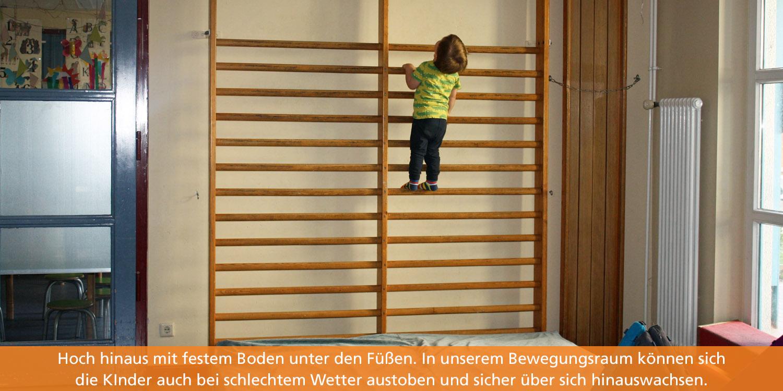Ein kleines Kind klettert eine Sprossenwand hinauf. Unter der Sprossenwand liegen große, weiche Matten.