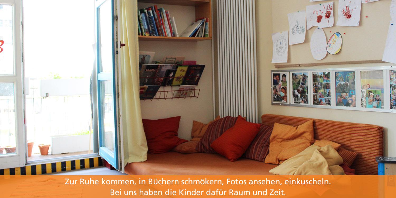 In der Ecke des Gruppenraumes liegt eine Matratze, auf der die Kinder entspannnen, lesen und sich ausruhen können. An der Wand hängt eine Regal mkit Büchern. Das Fenster ist geöffnet und lässt Tageslicht hineinstömen.