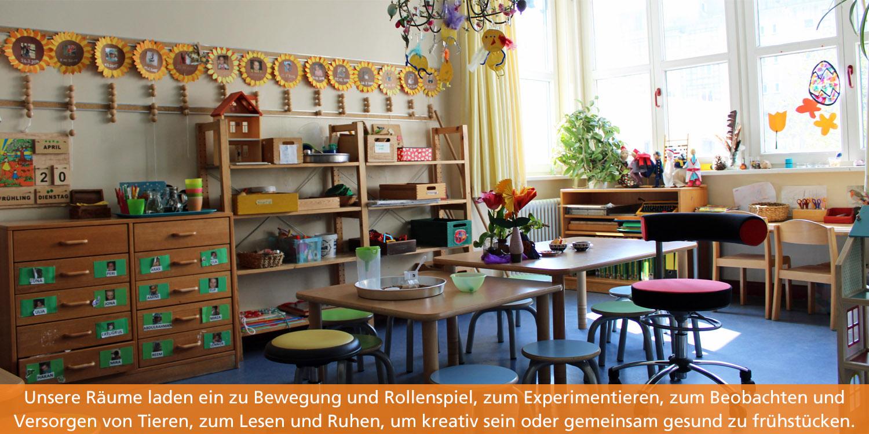 Im Gruppenraum stehen zwei Tische mit kleinen Hockern drumherum. In den Rageln stehen Farben, Pinsel und andere Kreativmaterialien.