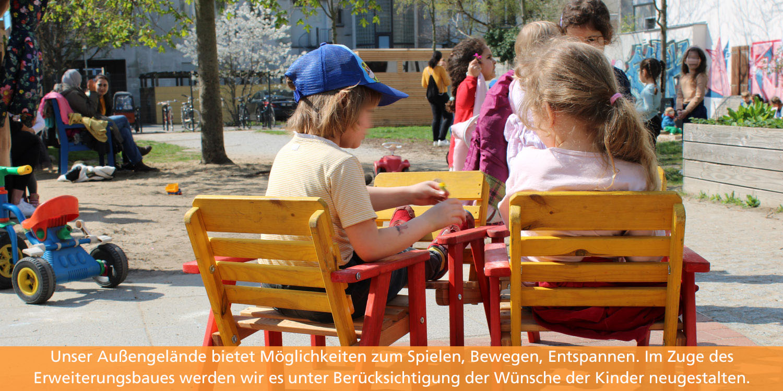 Fröhliches Treieben im Garten. Zwei Kinder sitzen im Vordergrund an einem Tisch und unterhalten sich.