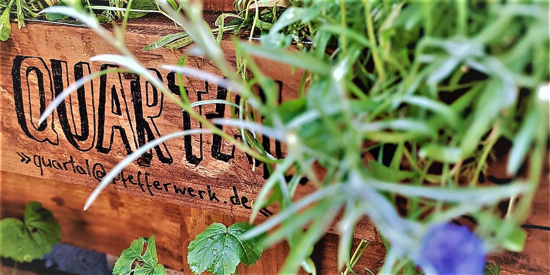 """Holzbrett mit """"Quartal"""" hinter einer Grünpflanze"""